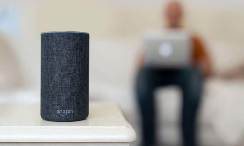 Amazon Echo with a man in the background.